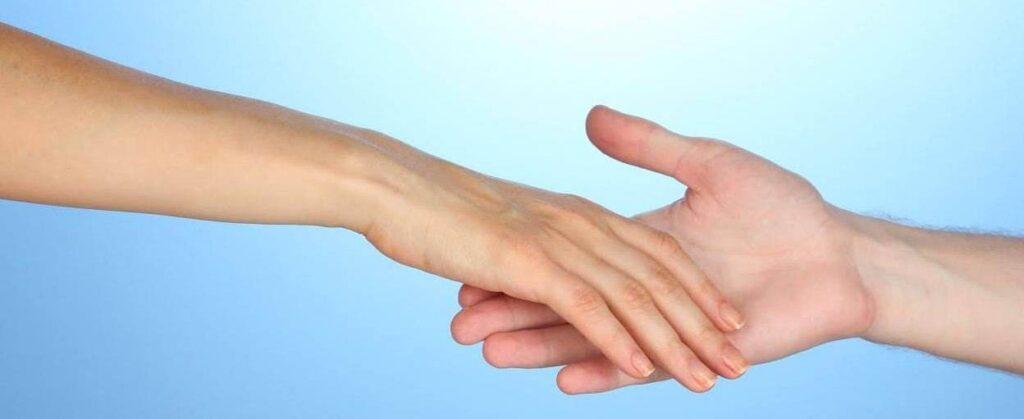 Doua persoane dand mana pe un fundal albastru
