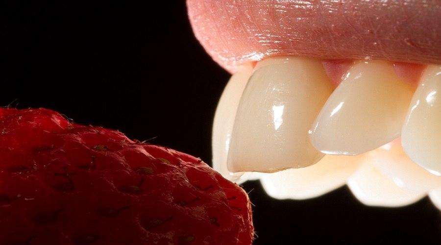 Femeie cu dinti albi muscand dintr-o zmeura si riscand patarea dintilor